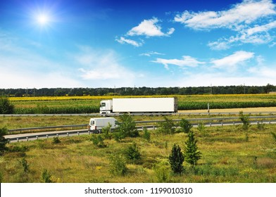 White truck with a white trailer and a van on the countryside road with fields and forest against blue sky with clouds and sun