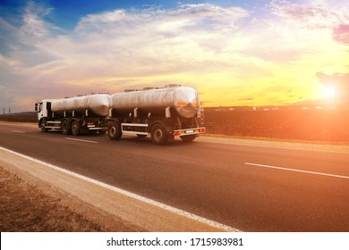 White truck witha trailer shipping milk on a countryside road against a night sky with a sunset