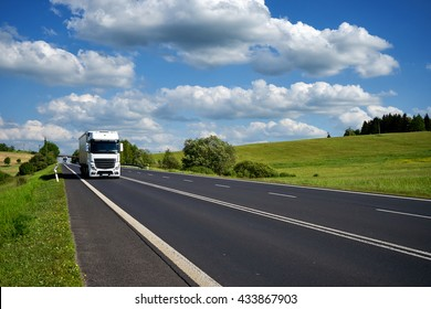 White trucks driving on asphalt road in a rural landscape. Sunny day with blue skies and white clouds over green meadows.