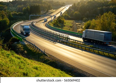 White trucks passing through tollgates on the highway winding through the wooded valley in backlit. View from above.