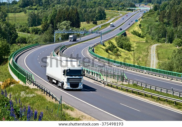 White trucks traveling on the asphalt highway with electronic toll gates in a wooded landscape. View from above. Sunny summer day.