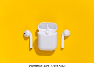 White true wireless bluetooth headphones or earbuds with charging case on yellow bright background. Top view