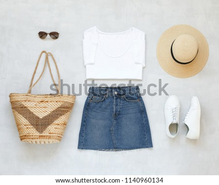 White t-shirt, blue denim mini skirt, wicker straw bag, brimmed boater hat, white sneakers on grey background. Woman's casual outfit. Flat lay, top view. Trendy simple summer minimalistic look.