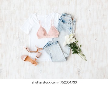 White t-shirt, blue jeans, pink lace triangle bra, pink block heeled sandals, flowers on white wooden background. Overhead view of woman's casual outfit. Simple basic women clothes. Flat lay, top view