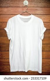 White t-shirt hang on wood wall.