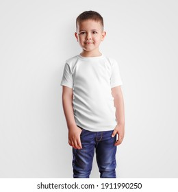 White t-shirt mockup on handsome boy in blue jeans, blank clothes for design and pattern presentation. Casual kidwear template isolated on background. Child posing for advertising branded clothing