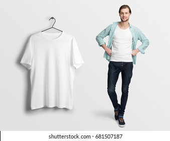 White t-shirt on a man in jeans, wearing checked shirt, isolated, mockup. Hanging blank t-shirt, against empty wall.