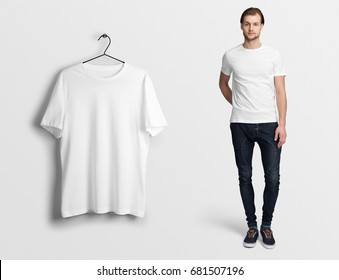 White t-shirt on a man in jeans,isolated, mockup. Hanging blank t-shirt, against empty wall.