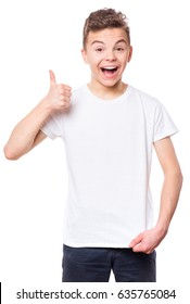 White t-shirt on teen boy. Handsome smiling child making thumbs up gesture, isolated on white background. Concept of childhood and fashion or advertisement design. Mock up template for design print.
