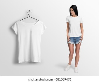 White t-shirt on a young woman in shorts, isolated, mockup. Hanging blank t-shirt, against empty wall.