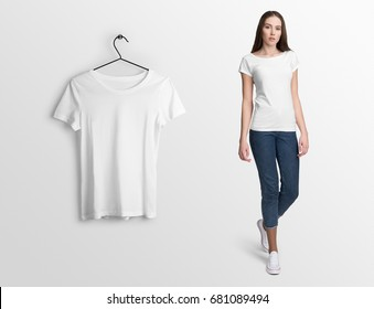 White t-shirt on a young woman in jeans, isolated, mockup. Hanging blank t-shirt, against empty wall.
