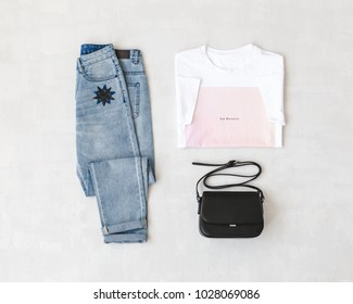 White t-shirt with pink print, blue jeans and small black cross body bag on grey background. Overhead view of woman's casual outfits. Flat lay, top view. Trendy hipster look.