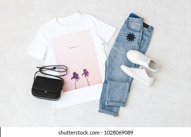 White t-shirt with pink print, blue jeans, small black cross body bag and white sneakers on grey background. Overhead view of woman's casual outfits. Flat lay, top view. Trendy hipster look.