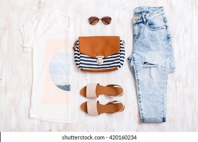 White t-shirt with print, light blue ripped boyfriend jeans, beige sandals, sunglasses, textile striped bag on white wooden background. Overhead view of woman's casual outfits. Flat lay, top view.