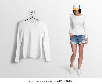 White t-shirt wide neck, long sleeves, on a young woman in shorts and cap, isolated mockup. Hanging t-shirt long sleeves, against empty wall background.
