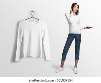 White t-shirt wide neck, long sleeves, on a young woman in jeans and hat, holding smartphone, isolated, mockup. Hanging t-shirt long sleeves, against empty wall background.