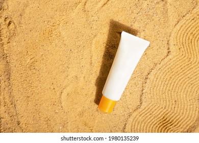 Weiße Tube mit Sonnencreme auf Strand Sand. Sonnenschutz. Draufsicht. Leerzeichen kopieren