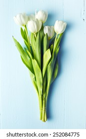 white tulip on blue wooden table