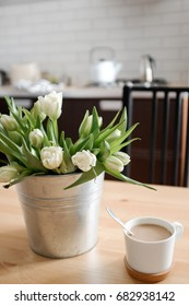 White tulips in an iron vase  in the kitchen next to a cup of coffee