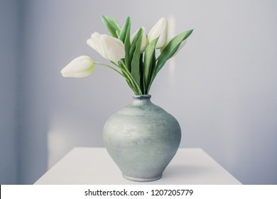White tulips in a jug on a table in the early morning in a room with gray walls
