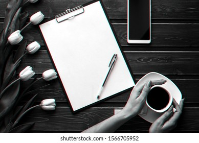White tulips on a wooden table with an empty paper tablet and smartphone and a Cup of coffee in women's hands. Flat lay, top view composition with copy space. 3D virtual reality glitch effect