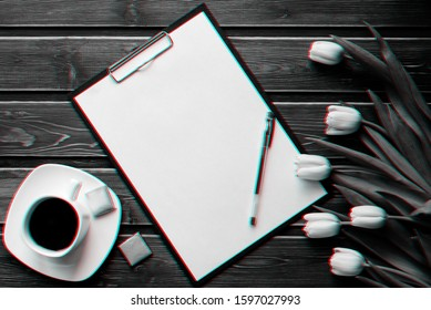 White tulips on a wooden table with a Cup of coffee and an empty paper tablet. Flat lay, top view composition with copy space. 3D virtual reality glitch effect