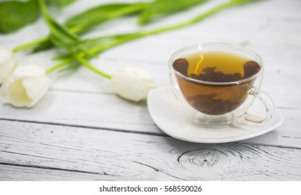 White tulips and transparent Cup of tea on wooden background,holiday concept