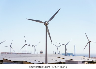 White turbines at wind farm with power station and sea in background, arid landscape on sunny summer day, sustainable renewable electricity concept