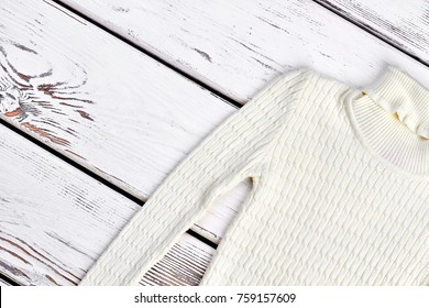 White turtleneck texture design sweater. High quality white knitted sweater for kids on old wooden background. Kids winter fashion knit clothes.