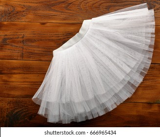 White tutu skirt on wooden background with empty space for text