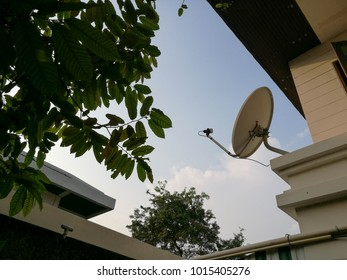 White TV and Internet satellite dish installed on the wall of the house.