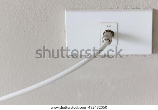 White tv plug antenna electronic on white wall background.
