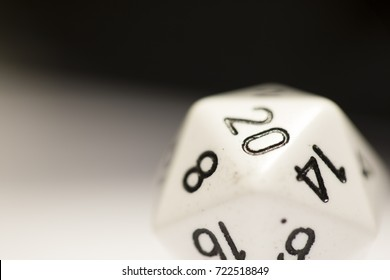 A white twenty-sided die with a 20 showing, on its side.