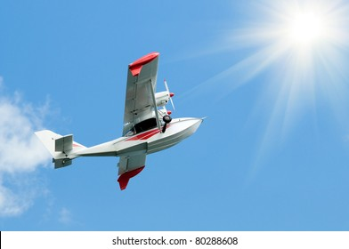 white twin-engine  light   hydroplane make flight, aloft in blue sky