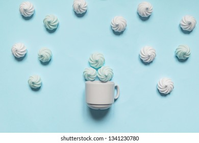white twisted meringues in porcelain bowl on blue background, greeting card, copy space