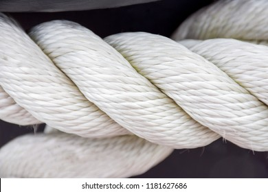 White twisted sea rope close-up on a wharf in the summer