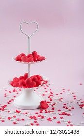 White two tier serving tray full of multicolor sweet sprinkles sugar candy hearts.  Love and Valentine's day concept.
