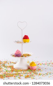 White two tier serving tray and miniature multicolored sugar cupcakes with sprinkles
