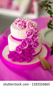 white two-tiered cake with roses made of mastic