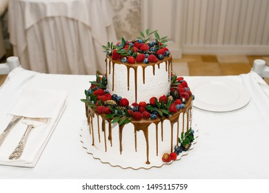 white two-tiered wedding cake with berries and smudges of ganache