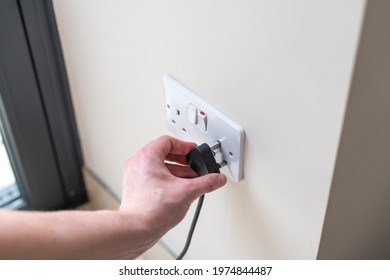 White Uk plug sockets being plugged into with a black plug and male arm