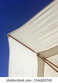 White Umbrella against brilliant blue sky