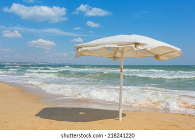 White umbrella on the beach with cloudy blue sky in background