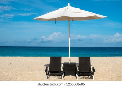 White Umbrellas and Black Chairs on a Caribbean Beach on a Sunny Day
