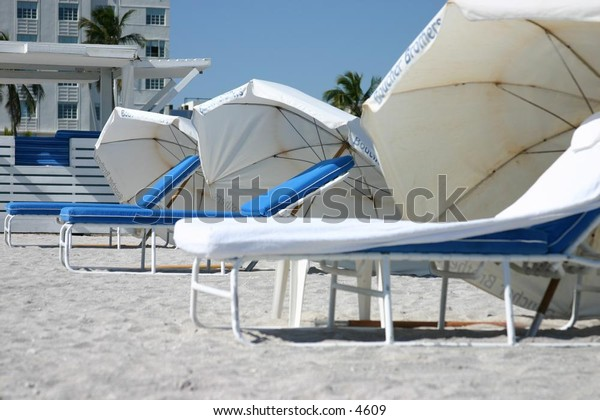 white umbrellas and lounge chairs on sandy beach