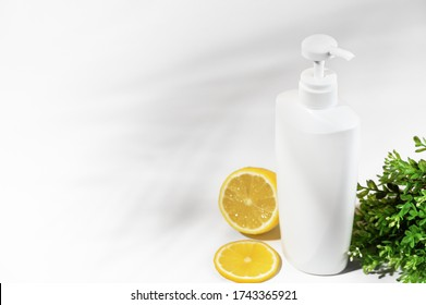 White unbranded bottle with lemon and green plants. Container with dispenser natural cosmetic products. Blank flacon for lotion, cream, body lotion, shampoo or hair conditioner. Mockup style