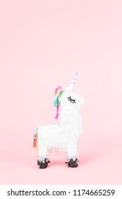 White unicorn pinata on a pink background.