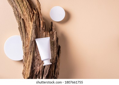 White unlabelled cosmetic bottle on dry wooden bark background. Skin care, organic body treatment, skin nutrition concept. Eco friendly product. Organic cosmetics. Moistening, dry skin concept.