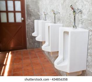 White urinals in men's public restroom.Selective focus.