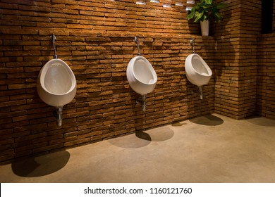 White urinals on brick wall in the men toilet